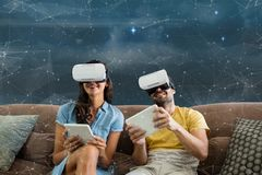 Happy couple in VR headsets sitting against galaxy background. Digital composite of Happy couple in VR headsets sitting against galaxy background stock photos