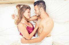 Happy couple waking up in love. Hugging and smiling to each other Royalty Free Stock Images