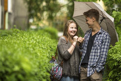 Happy couple on a walk in the park with umbrella. Royalty Free Stock Image