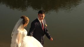 Happy couple walking along river bank. Loving groom in suit and bride in white dress are walking on beach. Concept of a stock footage