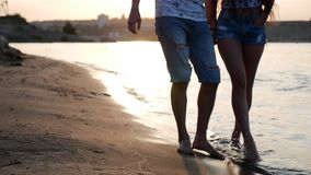 Happy couple holding hands strolling along the shore, walking on the sand barefoot on the sea waves, hugging.