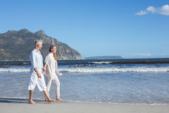 Happy couple walking barefoot on the beach Stock Photography