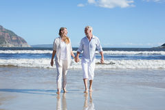 Happy couple walking barefoot on the beach Stock Photo
