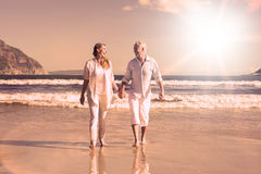Happy couple walking barefoot on the beach Royalty Free Stock Images