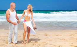 Happy couple walking on the beach. Young new family spends honeymoon at tropical resort, holding hands, handsome man & beautiful woman in love, vacation & Royalty Free Stock Image