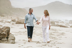 Happy Couple Walking On Beach Stock Image