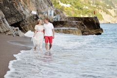 Happy couple walking on the beach of Positano in wedding day Royalty Free Stock Images