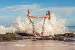 Happy couple walking at the beach, sea view. Traveling at Bali. Honeymoon summer travel at Indonesia Stock Photo