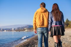 Happy couple walking at the beach on a sunny Royalty Free Stock Photos