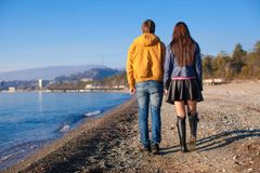 Happy couple walking at the beach on a sunny Stock Images