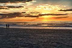Happy couple walking on the beach at sunrise for holiday time Royalty Free Stock Photography