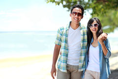 Happy couple walking by the beach together in love holding aroun Stock Photos