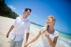 Happy couple walking on beach. Royalty Free Stock Photography