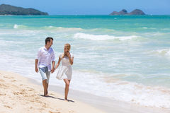 Happy couple walking on beach. Stock Photo