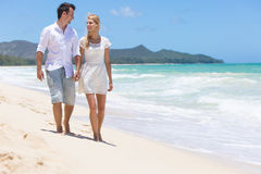 Happy couple walking on beach. Stock Photos