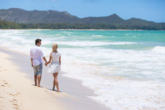 Happy couple walking on beach. Royalty Free Stock Images