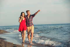 Happy couple walking on beach. Young happy couple walking on beach smiling holding around each other Royalty Free Stock Photography