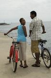 Happy Couple Walking With Bicycles On Beach Stock Photography
