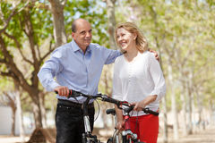Happy couple walking with bicycles Stock Photography
