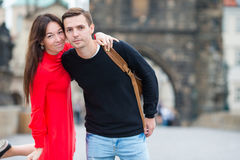 Happy couple walking on the Charles Bridge in Prague. Smiling lovers enjoying cityscape with famous landmarks. Happy tourist couple, men and women traveling on royalty free stock photo