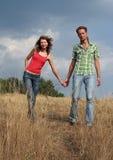 Happy couple walking on a field stock image
