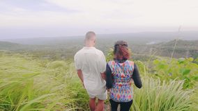 Happy couple walking on green mountain edge with beautiful landscape. Young man and woman enjoying amazing landscape stock video