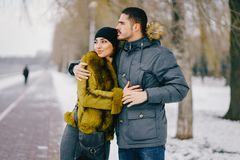 Happy couple walking through the park on a sunny winter day. Happy couple walking by the lake in the park on a sunny winter day Royalty Free Stock Photography