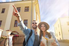 Happy couple walking outdoors sightseeing and holding a map. Royalty Free Stock Photo