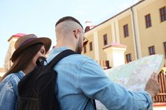 Happy couple walking outdoors sightseeing and holding a map. Stock Photography