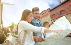 Happy couple walking outdoors sightseeing and holding a map. Happy couple walking outdoors sightseeing and holding a map Stock Images