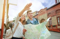 Happy couple walking outdoors sightseeing and holding a map. Happy couple walking outdoors sightseeing and holding a map Royalty Free Stock Images