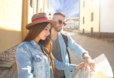 Happy couple walking outdoors sightseeing and holding a map. Royalty Free Stock Photography