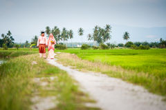 Happy couple walking at padi field Royalty Free Stock Photo