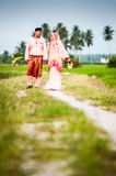 Happy couple walking at padi field Stock Photo
