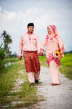 Happy couple walking at padi field Royalty Free Stock Photos