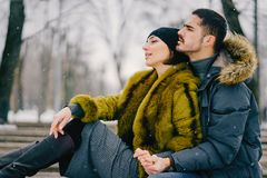 Happy couple walking through the park on a sunny winter day. Happy couple hugging and sitting on a bench in the park on a sunny winter day Royalty Free Stock Image