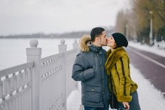 Happy couple walking through the park on a sunny winter day. Happy couple kissing and walking through the park on a sunny winter day Stock Photo