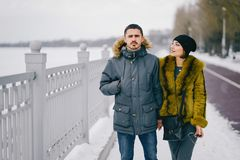 Happy couple walking through the park on a sunny winter day. Happy couple walking by the lake in the park on a sunny winter day Royalty Free Stock Image