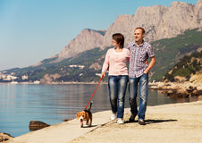 Happy couple walking with puppy on the seacoast Royalty Free Stock Image