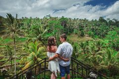 Happy couple walking at the rice terraces. Traveling at Bali. Happy couple walking at the rice terraces, holds hands. Traveling at Bali. Honeymoon summer travel stock photography