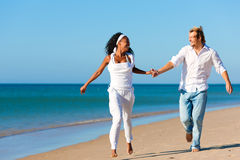 Happy couple walking and running on beach Royalty Free Stock Photos