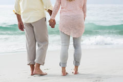 Happy couple walking by the sea Stock Photography