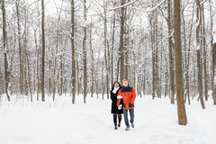 Happy couple walking through a snowy forest in winter Royalty Free Stock Photos