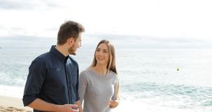 Happy couple walking and talking on the beach stock footage
