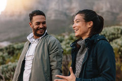 Happy couple walking and talking in the countryside. Portrait of happy young couple walking and talking in the countryside. Young men and women enjoying on a stock photography