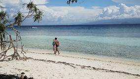 Happy couple walking on a tropical beach. Happy couple embracing walks on beautiful tropical beach by the sea on a tropical island.Travel concept.Family,summer stock video footage