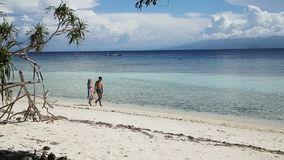 Happy couple walking on a tropical beach. Happy couple embracing walks on beautiful tropical beach by the sea on a tropical island.Travel concept.Family,summer stock footage