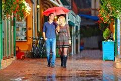 Happy couple walking under the rain Royalty Free Stock Photos