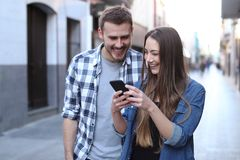Happy couple walking using cell phone in the street stock image