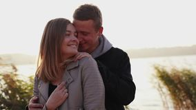 Happy couple walks on the quay at evening, smiles and kisses each other stock video